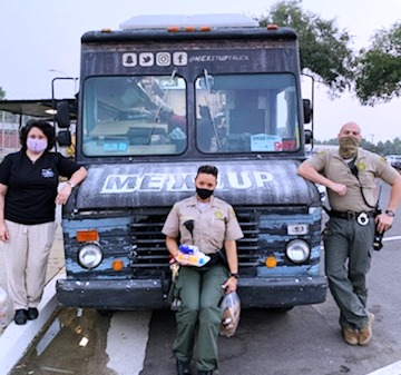 Three people wearing masks at a food truck.