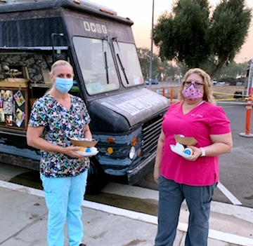 Two masked women at a food truck.