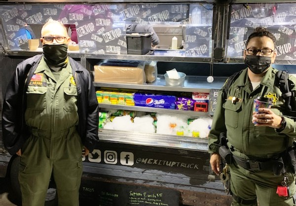 Two correctional officers wearing masks at a food truck.