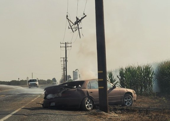 Jessica Macias Mercado assisted at an accident scene. The car is shown smoking and a telephone pole is down.