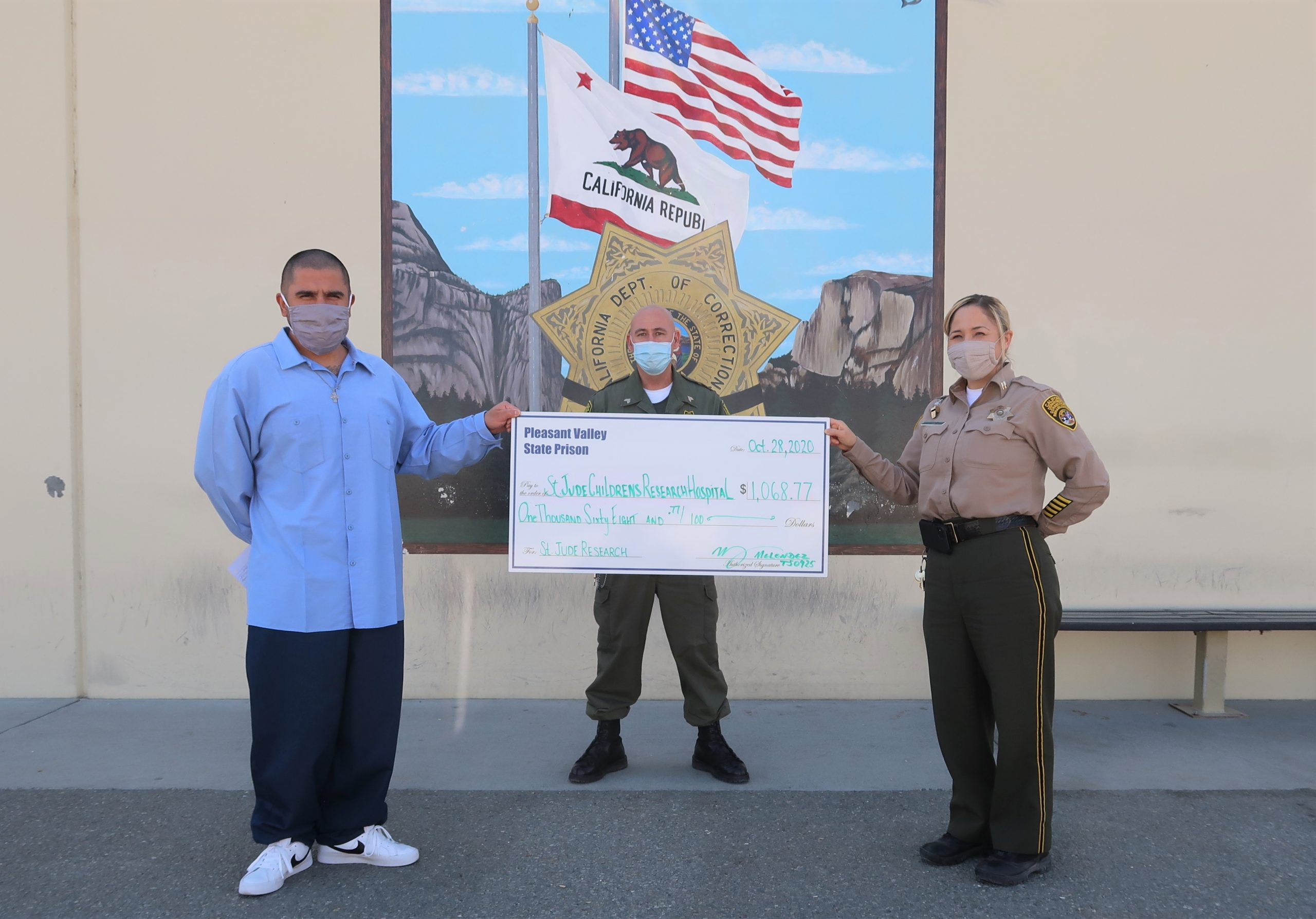 The prison population donated money to St. Jude, shown in a large check held by an inmate and two prison staff members.