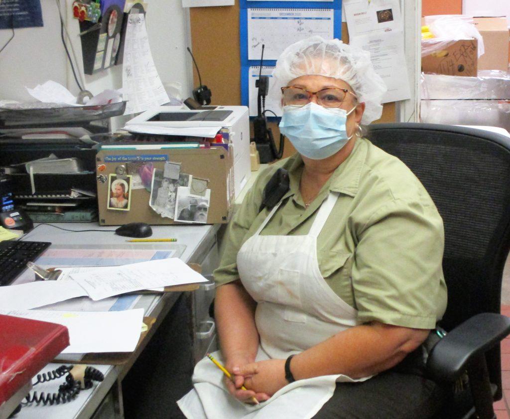 Supervising Cook Barbara Moreau sits at a desk at Pine Grove camp.