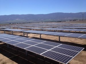 Solar panel projects near a prison, mountains in the background.
