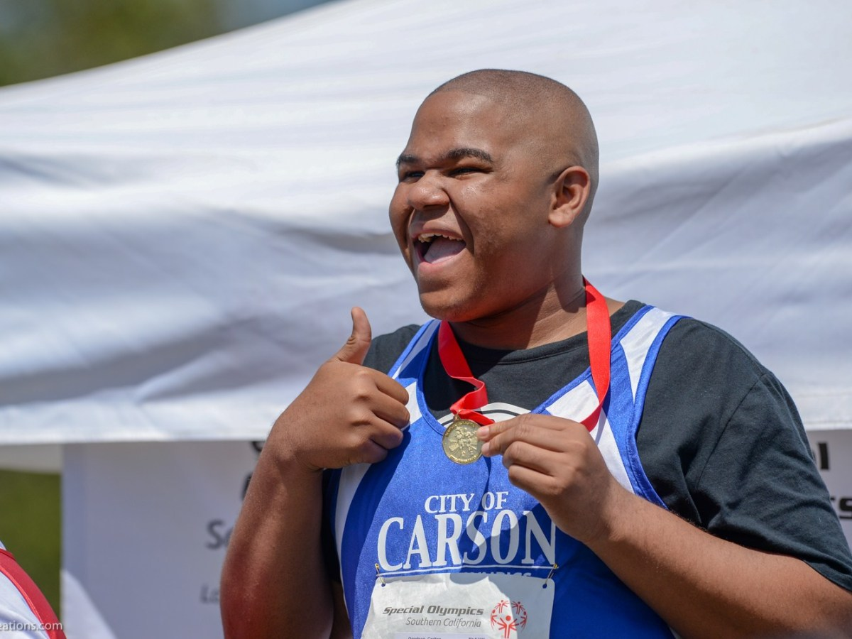 Special Olympics athlete smiles and gives a thumbs up.
