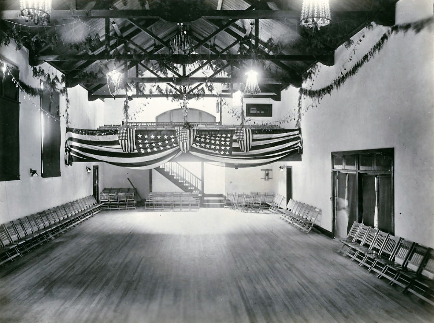 San Quentin social hall in 1919 shows flags and garland.