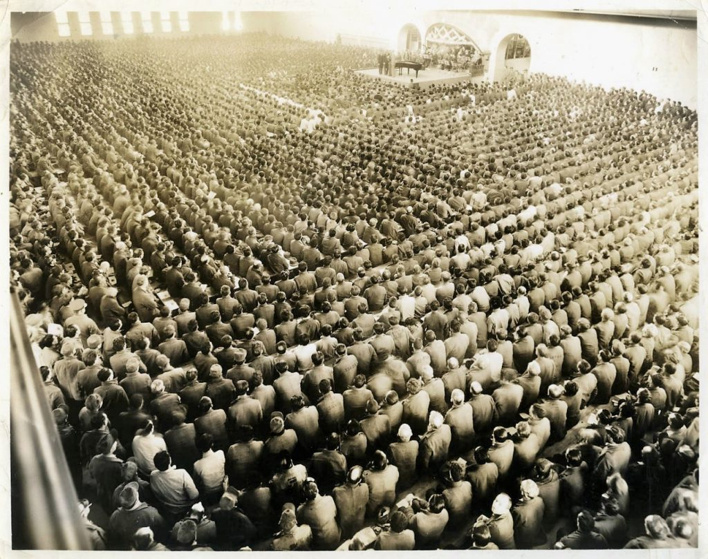 Overview photograph of 5,500 men in a large room to watch a performance.