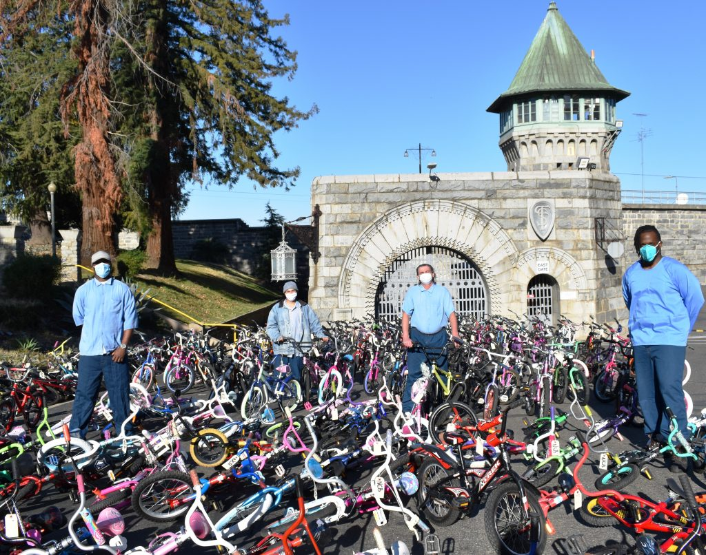 Four incarcerated men at Folsom Prison stand amid more than 50 bicycles.