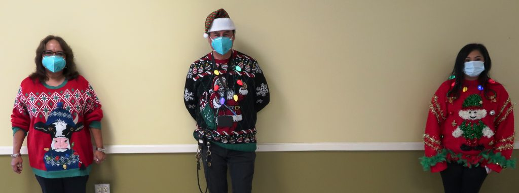 Three people wearing masking and holiday sweaters