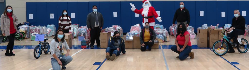 Ten masked people facing camera, including one dressed as Santa