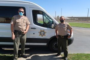 Correctional Officers Mayfield and Gomez stand in front of a CDCR transport .