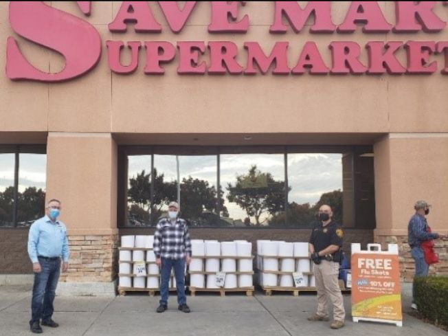 Four people stand in front of a store in Merced.