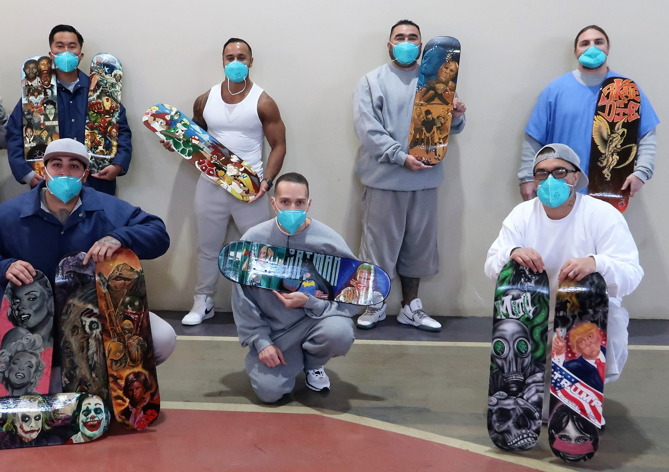 Incarcerated artists hold painted boards.
