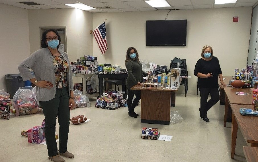 Three women wearing masks stand amid toys