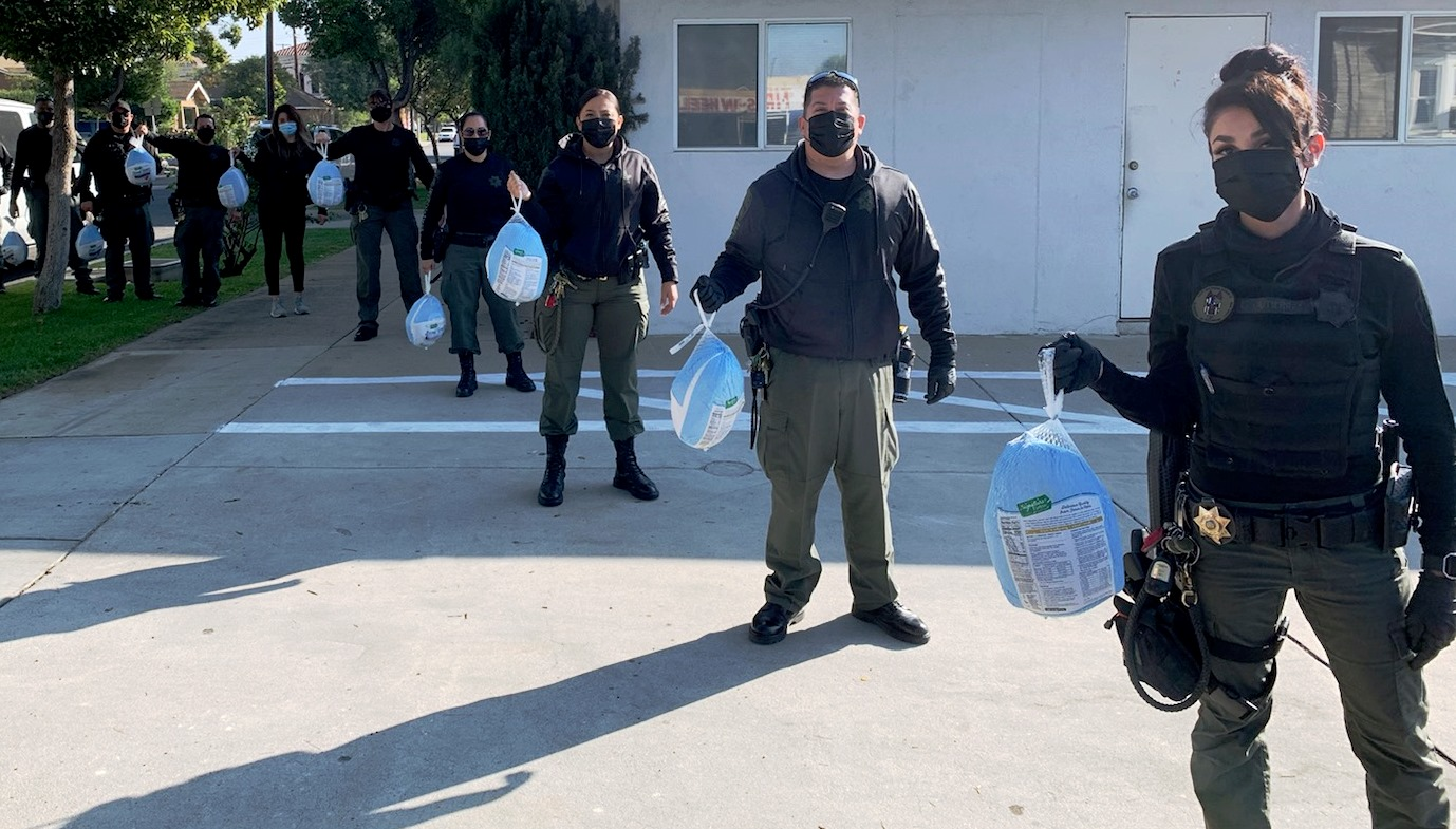 Line of CDCR officers each holding a frozen turkey.