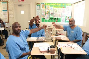 Incarcerated students hold models of DNA.