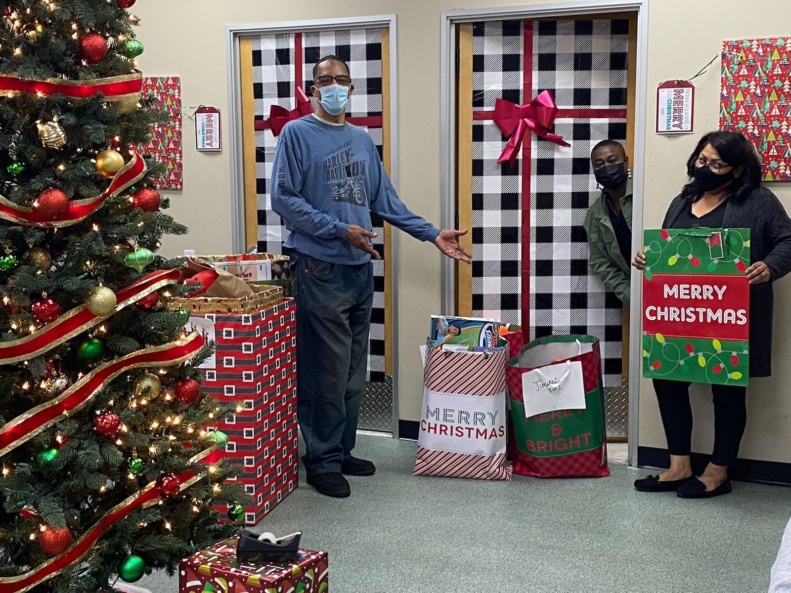 Three staff wear masks with holiday gifts, Christmas tree.