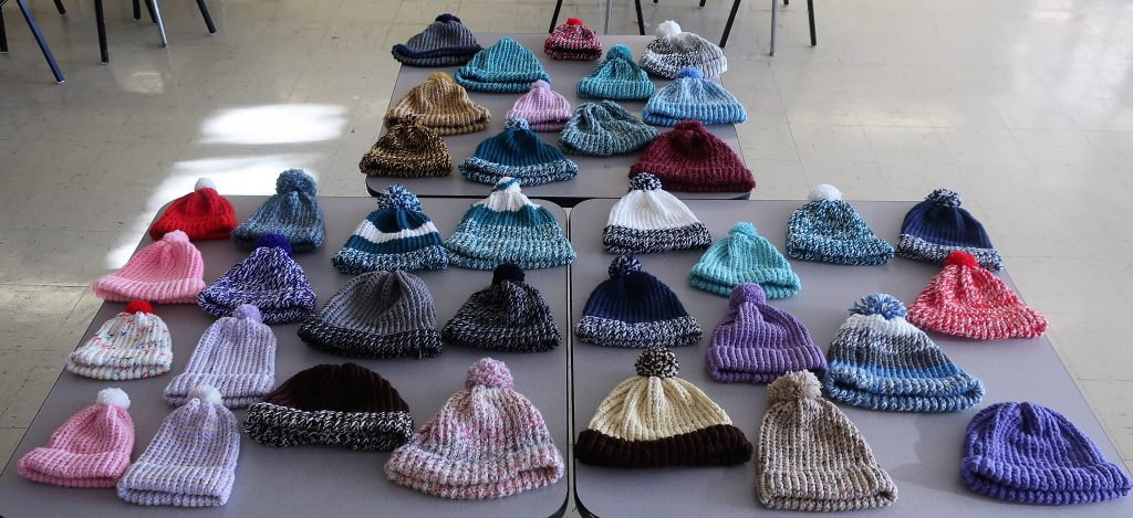 Beanies knitted by DJJ OH Close youth are displayed on tables.