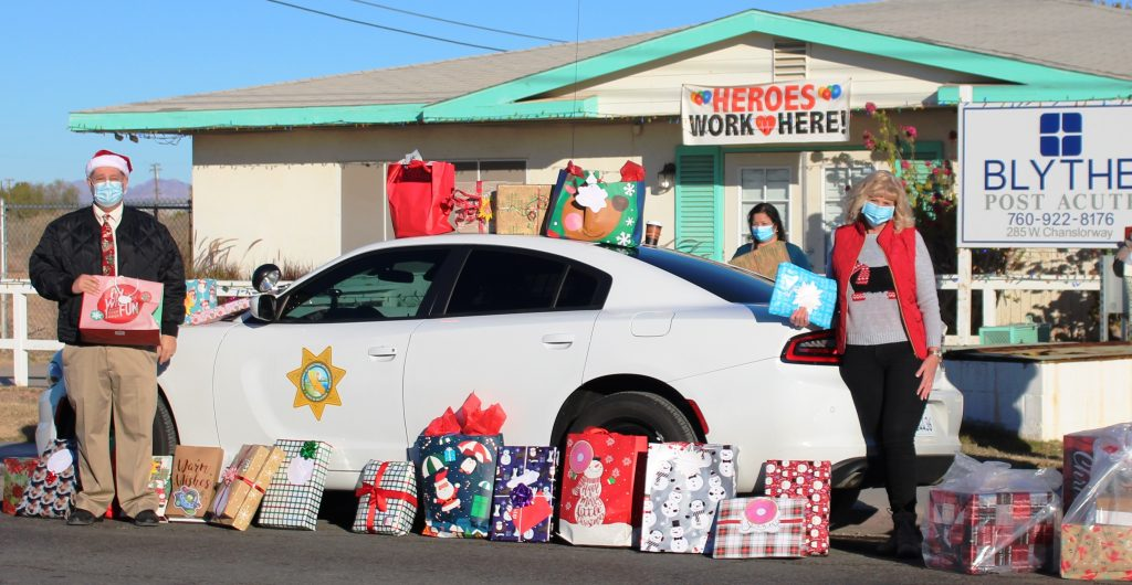 Two people standing next to a CDCR car with presents lined up next to the car