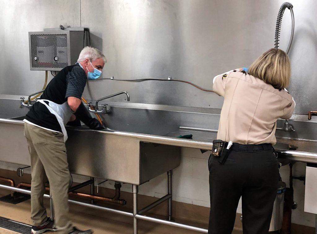 Mule Creek prison custody and non-custody staff wash dishes in the prison kitchen.