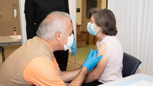 A doctor administers a vaccine to another person.