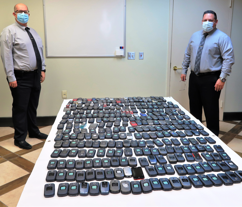 Two men in masks flanking a table with cell phones lined up in rows.