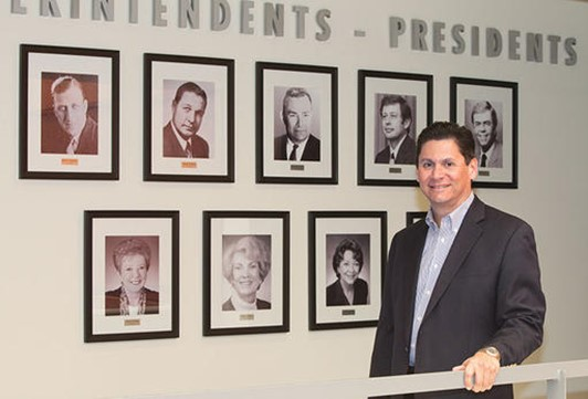 California Community Colleges chancellor stands in front of wall of photos.