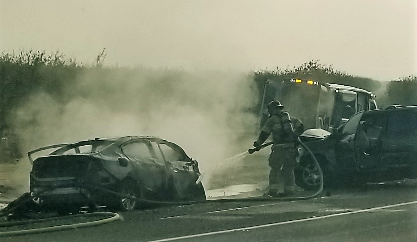 A firefighters extinguishes a car fire after people were pulled from the wreckage.
