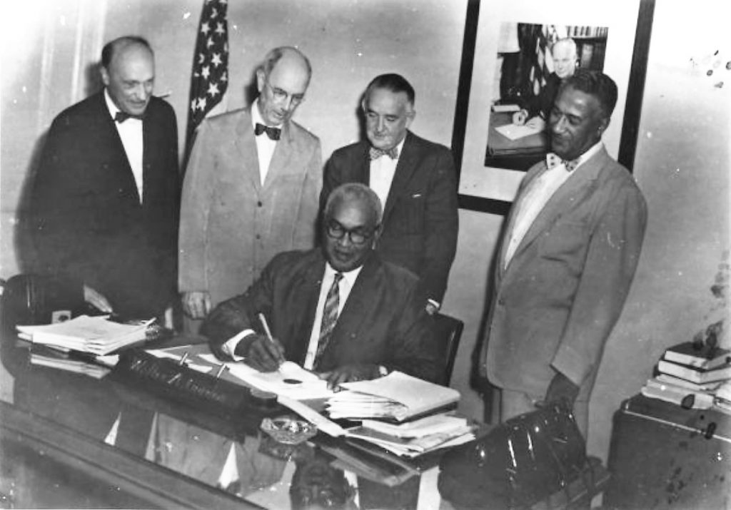 Walter Gordon sits at a desk while others watch him sign papers.