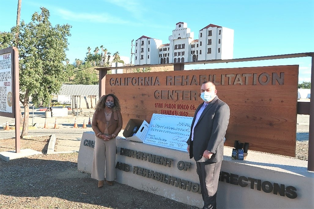 Woman and man wear masks and stand beside the California Rehabilitation Center sign.