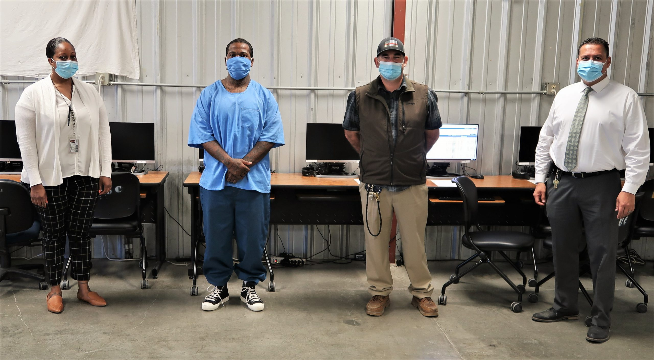 A Cyber High student and staff at Avenal State Prison stand in front of computers.