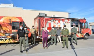Prison staff and a college president stand beside food trucks.