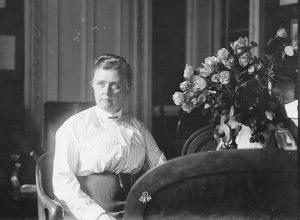 Woman sits in an office near flowers.