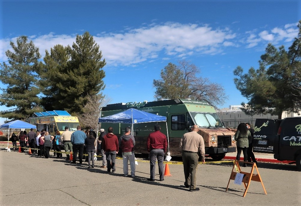 Prison staff stand in food-truck lines.
