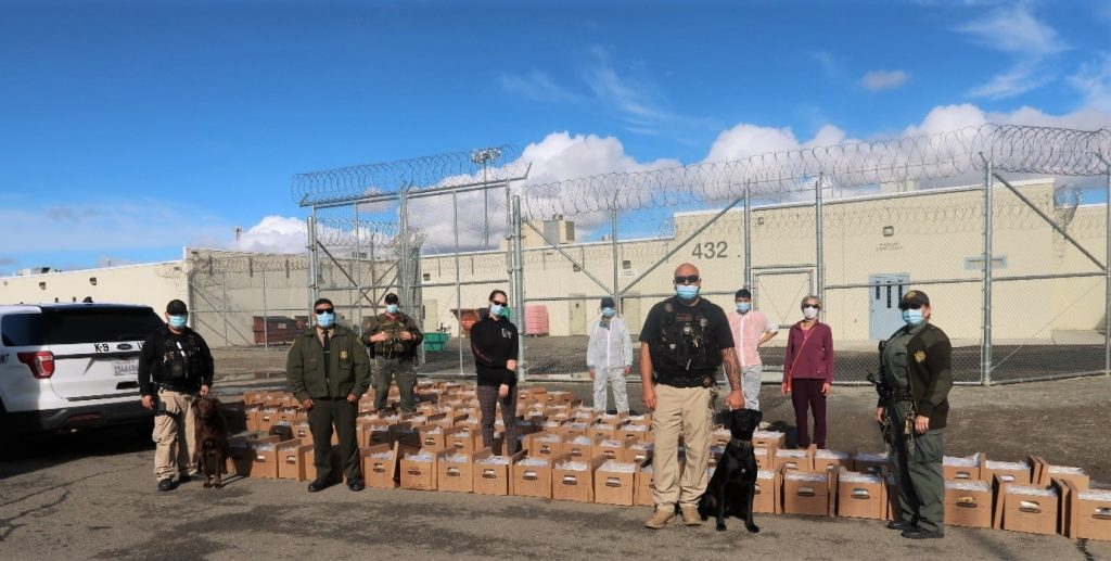 Prison staff stand beside boxes.
