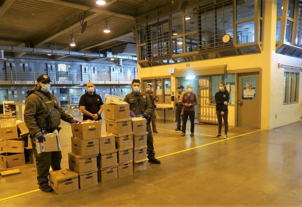 Prison staff with a stack of boxes.
