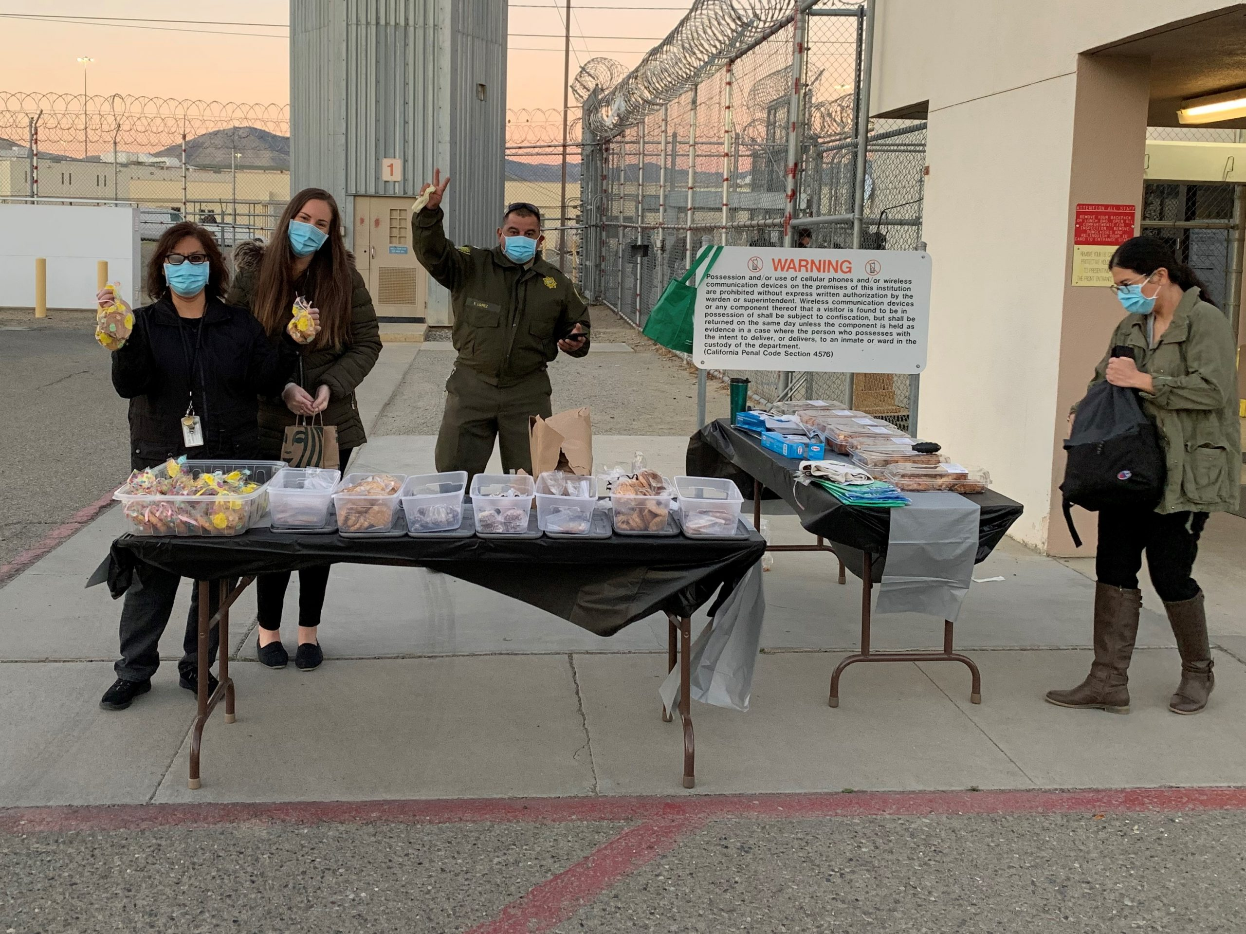Avenal prison staff stand at tables selling baked goods.