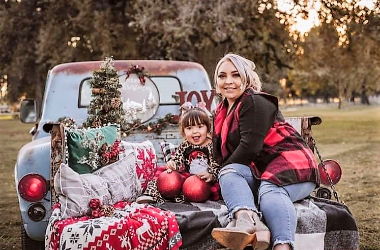 A mom and her daughter sit in the back of a pickup truck.