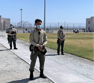 Correctional officers stop on a prison yard for a moment of silence.
