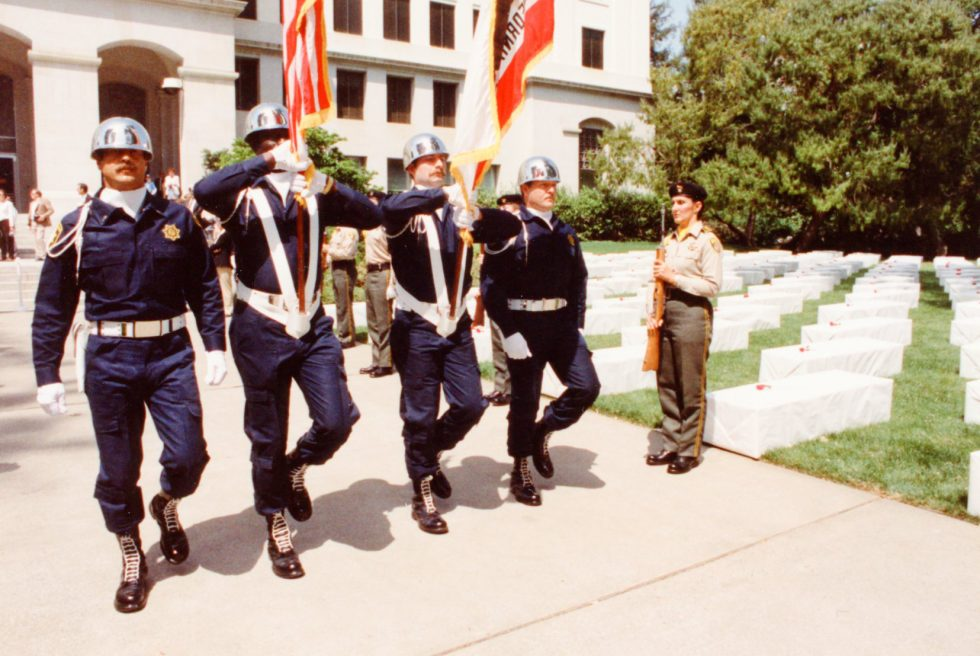 An honor guard carries flags at the California Capitol.