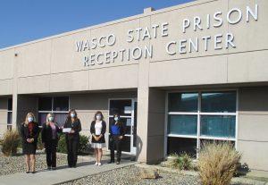 Prison staff donate a check to benefit Kern County crime victims.