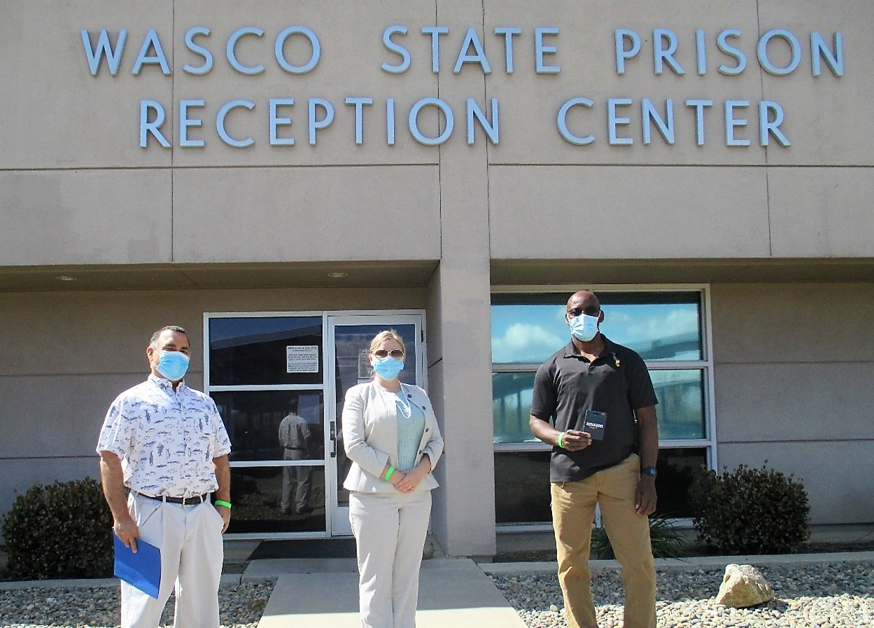 Two men and one woman stand in front of the Wasco State Prison Reception Center holding wellness challenge prizes.