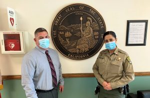 Two CDCR employees stand in front of a State of California seal.