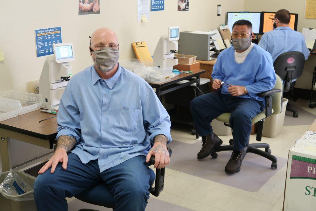 men sit at eyeglass stations.