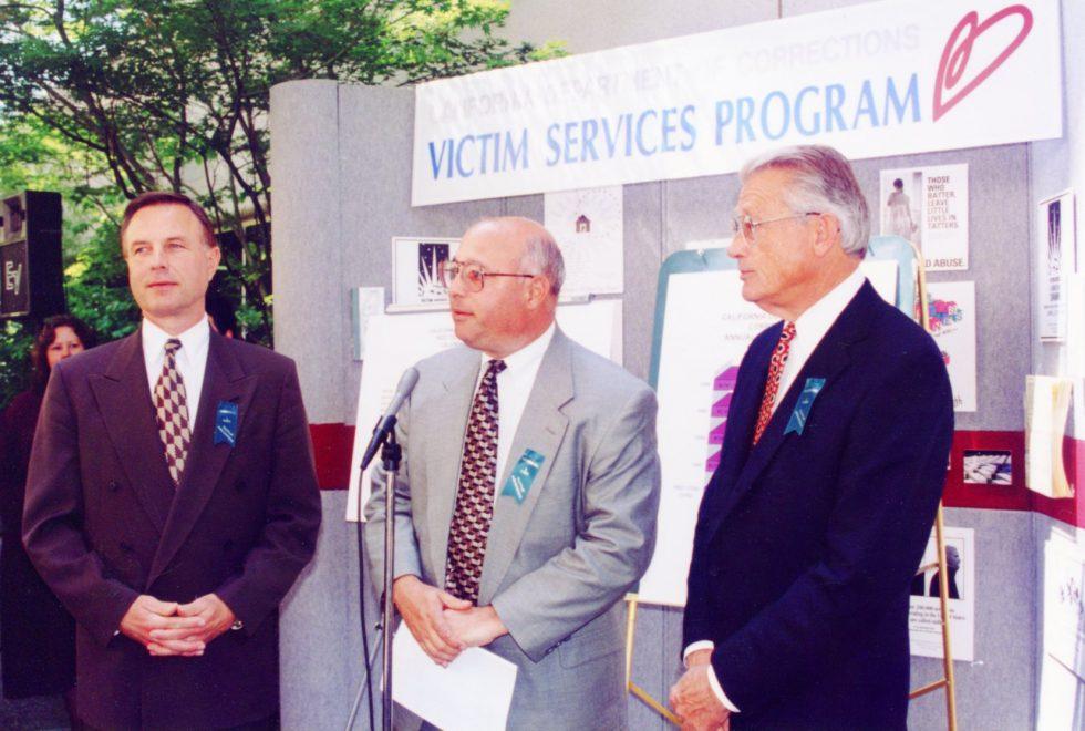 Three men speak in front of a Victim Services Program backdrop.