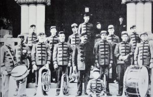 Preston School band students wear uniforms and stand on steps.