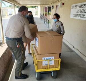 CIM employees push a cart of donations.