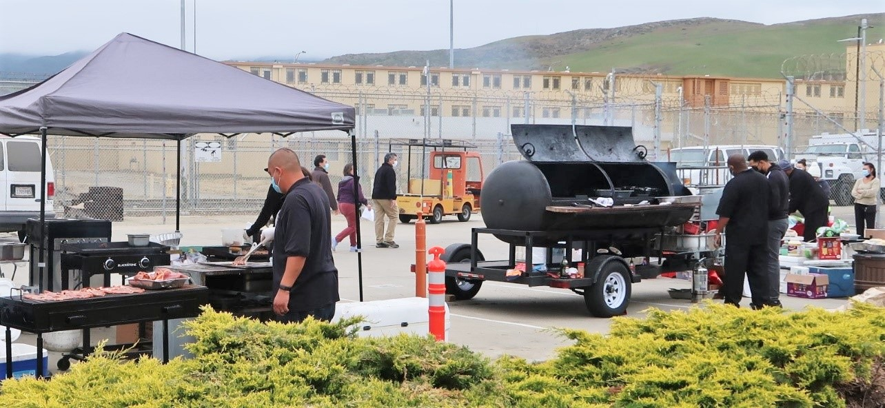Food truck workers grill meals for CMC staff. The prison can be seen in the background.