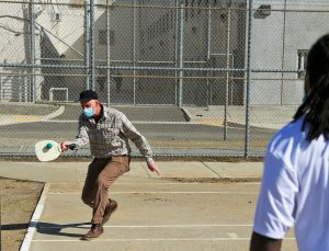 A recreation supervisor plays tennis at CMF, fencing and prison buildings can be seen in the background.