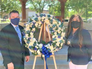 A man and woman wear masks and stand beside a wreath.