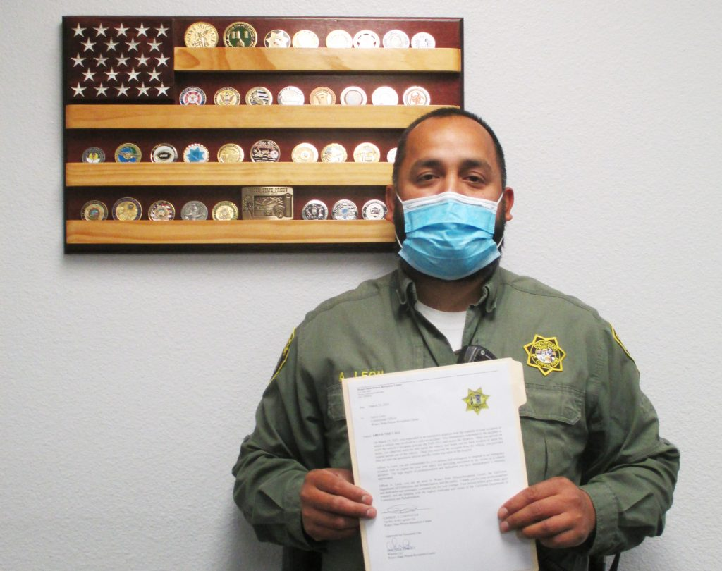 A correctional officer holds a letter.